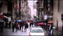 Slow motion footage of people walking down a wet roman street