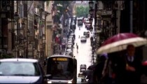 Cars and tourists traveling down a wet street in Rome