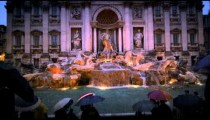Tourists visiting the Trevi Fountain at dusk in the rain