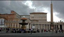 People walking around St. Peter's Square near a fountain and obelisk.