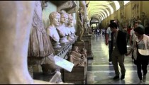 Tourists walk up and down the Gallery of Busts, including a couple who stops to look at a plaque.