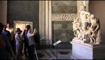 Tourists taking photos of a statue, the Laocoon.