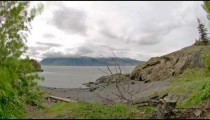 Time lapse view of clouds against a white sky with snow capped mountains in background, Alaska