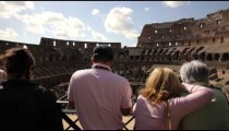 Tourists gazing from balcony to the bottom of the Colosseum.