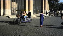 Tourists pose for pictures and ride by on a bike outside the Colosseum in Rome, Italy.