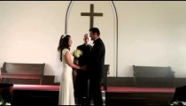 Preacher talking to a bride and groom in a chapel.