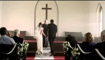 Father escorting bride to the groom at the front of a chapel.