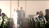 Guests applauding a newlywed couple walking up the aisle.