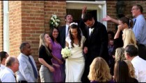 Slow-motion newlywed couple under thrown rice.
