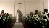 Bride and groom at the front of a chapel with a preacher.