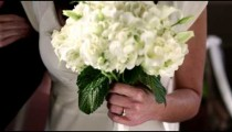 Shot of a bride's wedding ring and bouquet as she walks down the aisle.