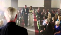 Father walking bride to the preacher at the front of a chapel.
