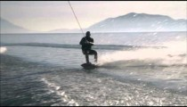 Slow motion lens flare shot of wakeboarder who wipes out