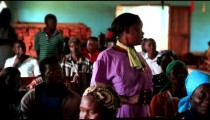 KENYA-C. 2012 A woman stands, speaks; others sit, listen during church in Kenya, Africa c.2012