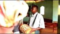 KENYA-C.2012 A man drums accompaniment for a singing congregation in Kenya, Africa c.2012.