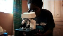 KENYA-C.2012 A woman looks through a microscope inside a medical clinic in Kenya, Africa c.2012.