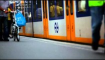 People walking along platform as train pulls up and stops