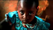 KENYA-C.2012 Little girl looks up at camera while recieving a snack in a Kenya, Africa c.2012.