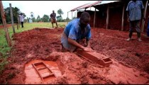 Man expertly shapes clay into brick molds; another carries wet brick to drying spot