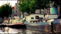 Tracking footage of barges docked along Amsterdam canal
