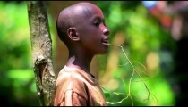 KENYA-C.2012 A young African boy sings while leaning against a sapling in Kenya, Africa c.2012