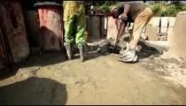 Men shoveling gravel aggressively.
