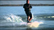 A wakeboarder makes a spray of water that covers him, then goes across a wake.