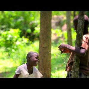 Two little african kids playing, laughing and jamming out in front of the camera in the forest