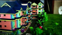 Handheld shot of a miniature scene of houses on display.