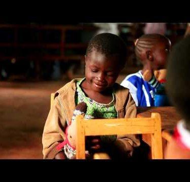 KENYA-C.2012 Cute African kids sit, hold stuffed animals in a Kenya, Africa school building c.2012.