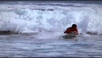 Slow motion shot of a man surfing towards the beach in Costa Rica