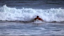 Slow motion shot of a young man surfing along the beach in Costa Rica
