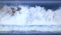 Slow motion shot of a long-haired surfer as he gets wiped out by the waves in Costa Rica