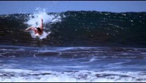 Slow motion shot of a woman paddling then standing on her surfboard as she surfs in Costa Rica