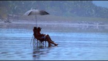 Slow motion static shot of a couple sitting on chairs under an umbrella on a beach in Costa Rica