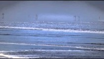 Slow motion shot of silhouetted people walking in the shallow part of the ocean at Costa Rica