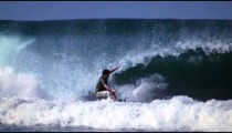 Slow motion shot of a male surfer riding a big wave and wiping out at a beach in Costa Rica