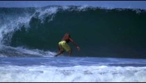 Slow motion shot of a long-haired surfer as he rides the waves in Costa Rica