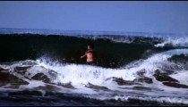 Slow motion shot of a male surfer who rides the wave and wipes out at a Costa Rican beach