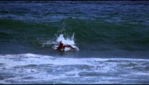 Slow motion shot of a paddling surfer who starts to stand up on a surfboard in Costa Rica