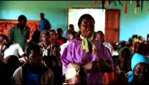 KENYA-C. 2012 A woman stands, speaks; others sit, listen during worship in Kenya, Africa c.2012