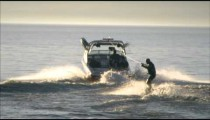 Slow motion long shot of a wakeboarder being towed by a boat