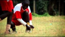 KENYA-C.2012 Young man crouches to adjust the laces of his football cleats in Kenya, Africa c.2012