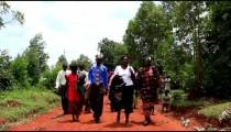 KENYA-C.2012 People walk toward and past the camera down a dirt road in Kenya, Africa c.2012