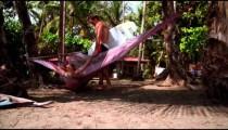Man holding surfboard kisses woman swinging in hammock