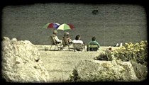 People sit at lake front. Vintage stylized video clip.