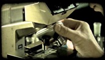 Man positions plate and looks into microscope. Vintage stylized video clip.