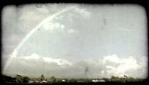 Rainbow over island town. Vintage stylized video clip.
