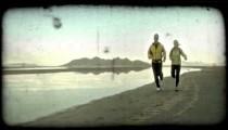 Couple jog along sand in desert. Vintage stylized video clip.