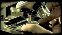 Hand places plastic plate under microscope. Vintage stylized video clip.